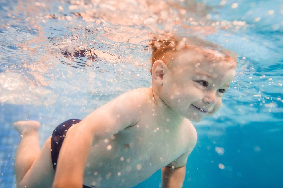 Little baby, boy swimming under water in