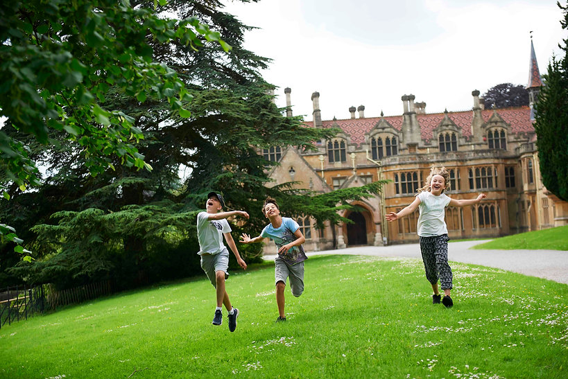 Visitors playing in front of Tyntesfield