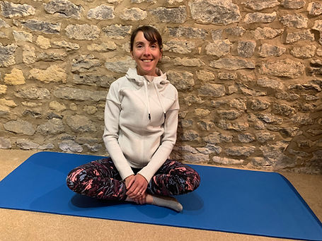 Pilates instructor sitting on mat