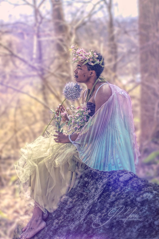 spring fairy sitting atop a boulder