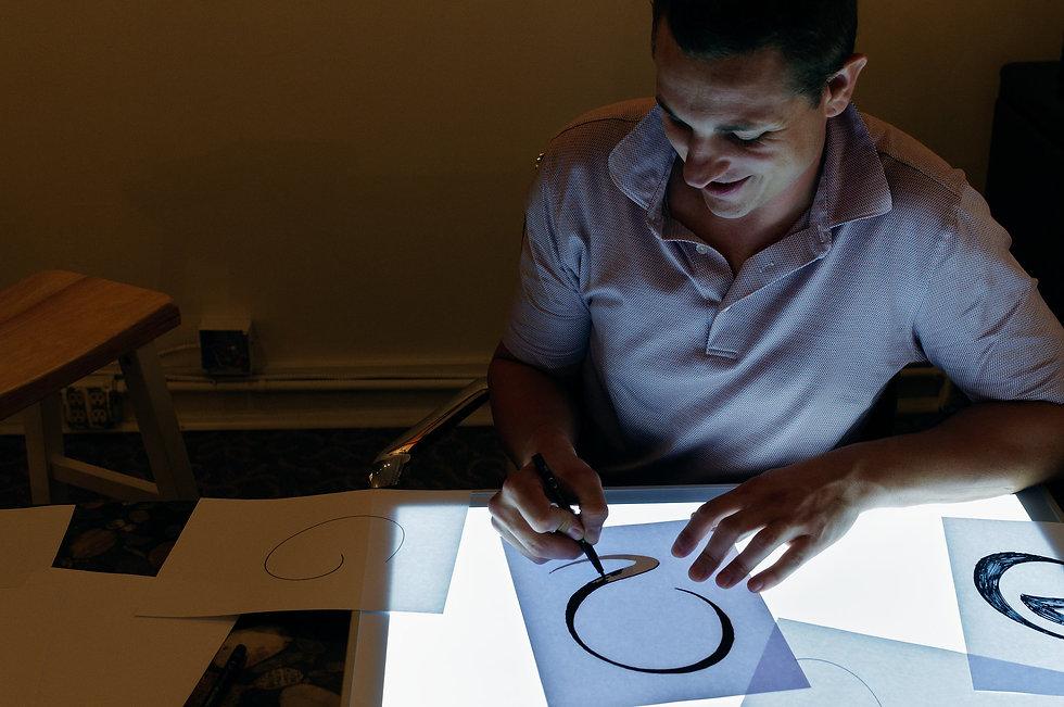 Artist Ryan Schmidt sketching new designs to fabricate in stainless steel