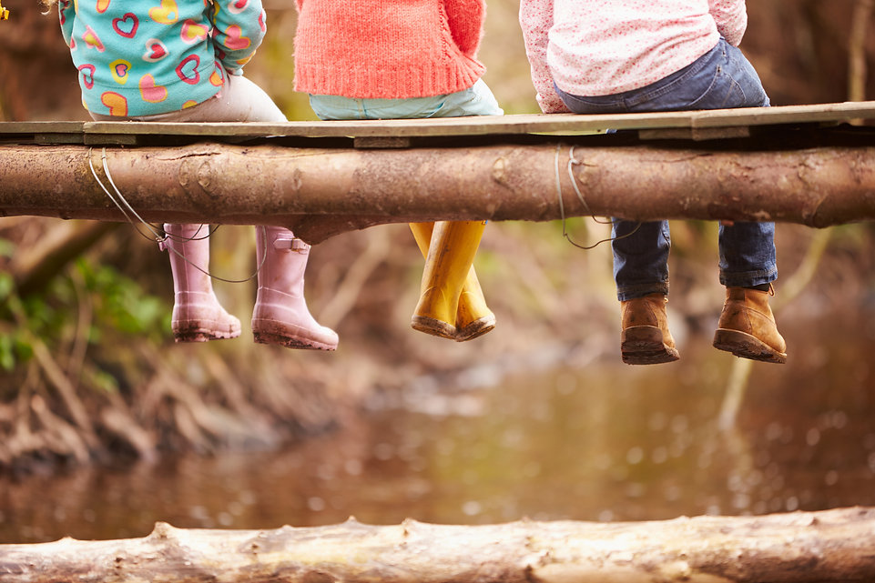 Close Up Of Children's Feet Dangling Fro
