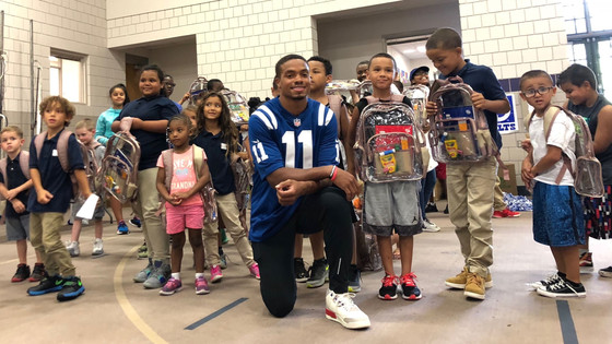 Ryan Grant distributes backpacks with school supplies to kids