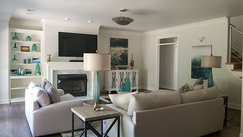Living area with white and gray sofa's and rug. The room has touches of color in wall décor, etc.