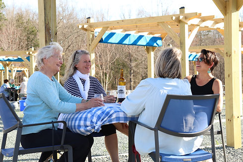 Four older ladies sitting outside enjoying warm weather and a glass of wine.