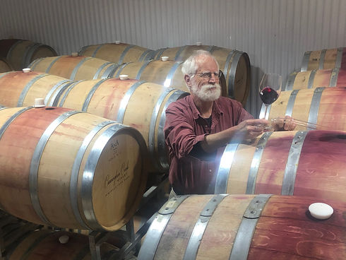Bruce Deal among various wine barrels, inspecting wine