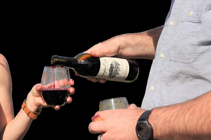 man pours merlot wine in a short wine glass