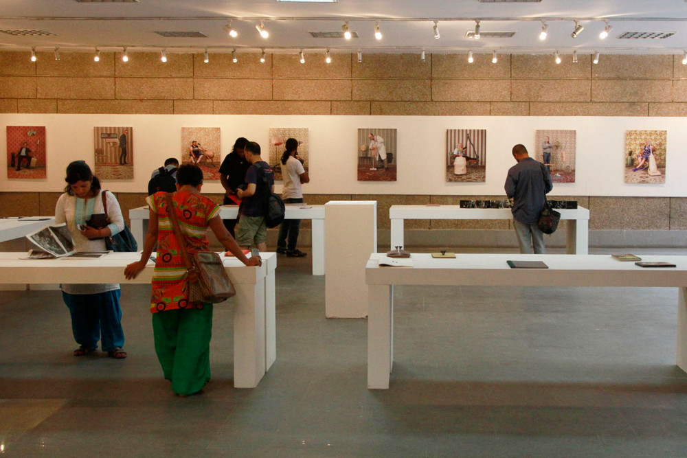 """Visitors browse through books at """"Looking Eastward"""", an exhibition of self-published works curated by Sohrab Hura, and books on display by Photoink."""