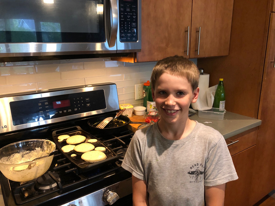 Miles runs the pancake griddle with Allison