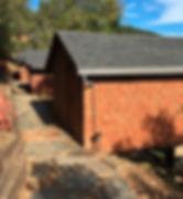 Stone pathway to three shingled cabins