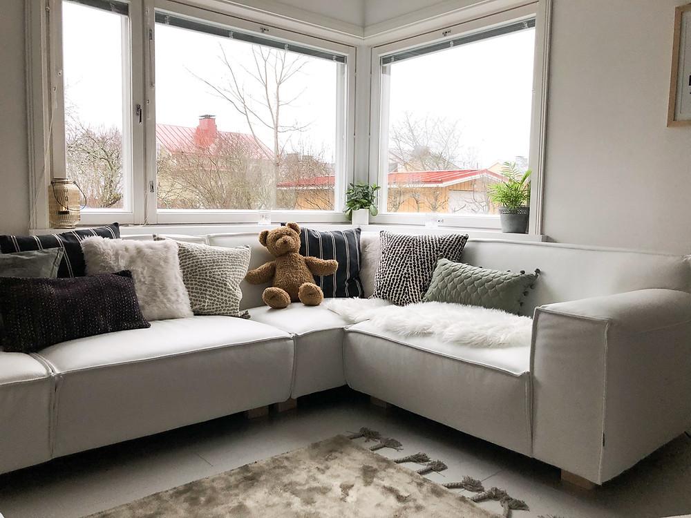 Kunnostetut kulmaikkunat funkkistalossa ja H&M Homen tyynynpäälliset Furninova Vesta -sohvan päällä