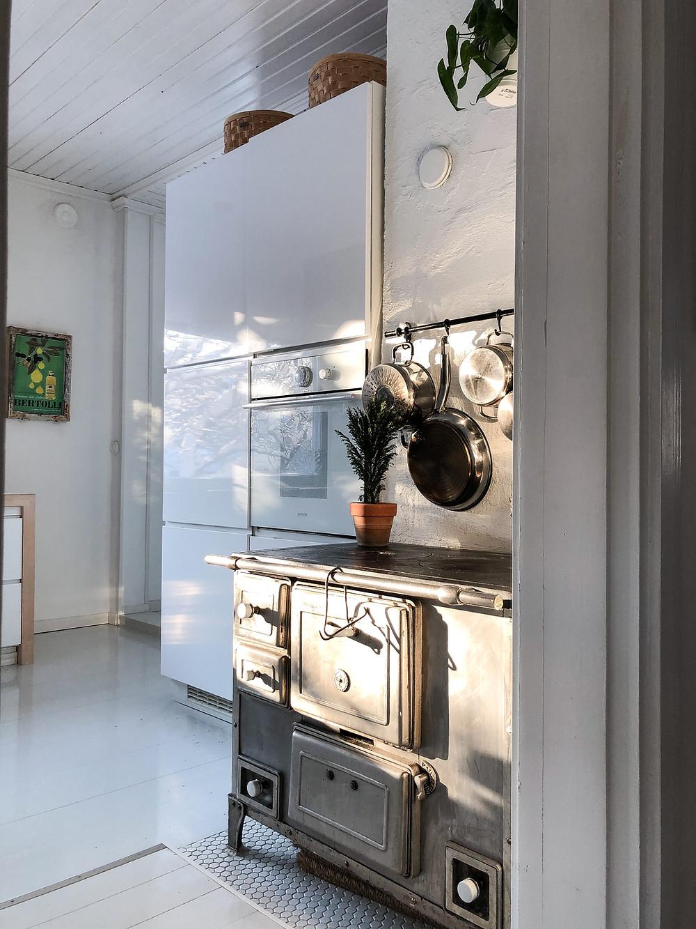 vanha liesi keittiössä, integroidut kodinkoneet, vaaleanharmaa lautalattia, light grey wooden floor, old stove in kitchen