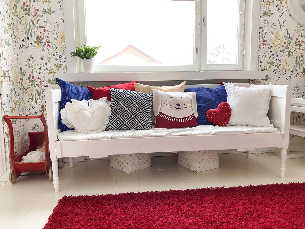 Vanha penkki ja punainen matto lastenhuoneen sisustus