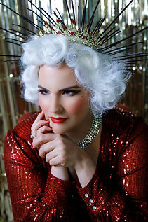 Sugar St Claire - a woman sits front on to the camera in a red sequin gown, wearing a gold and red crown and white vintage-styled wig. Image and styling by Rachel Mia Photography