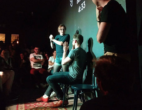 Group of improv performers playing out a scene on stage