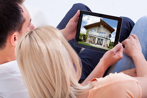 Couple Looking At House On Digital Table
