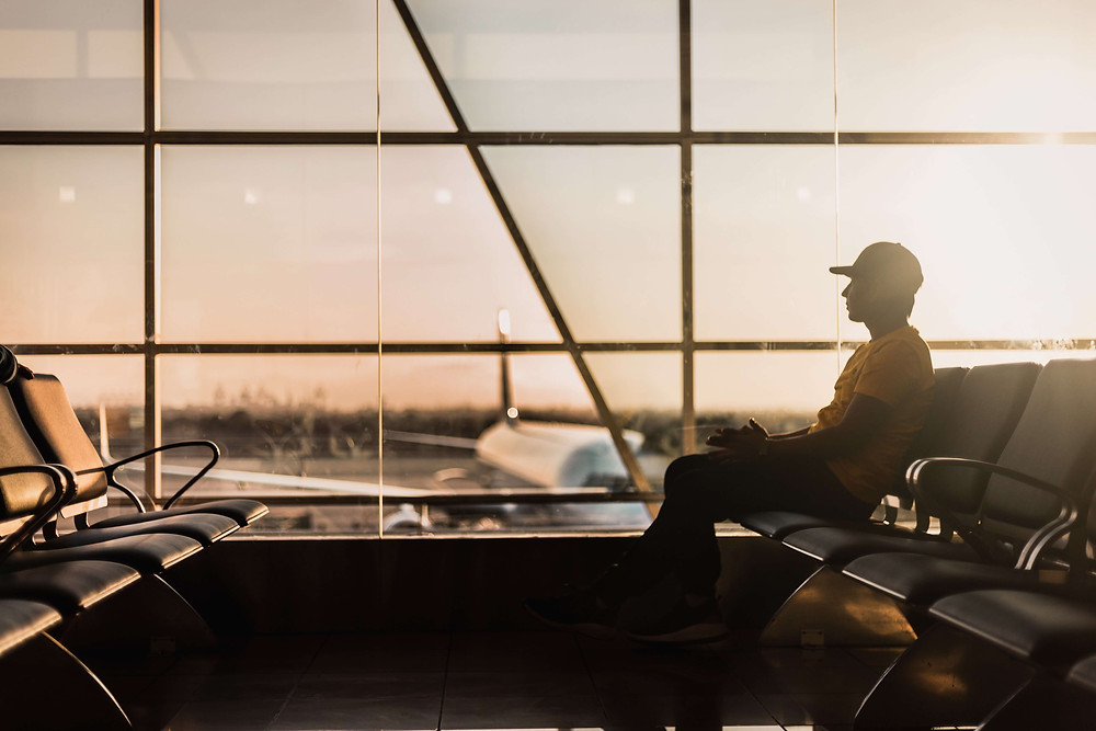 A man waiting in an airport during the golden hour