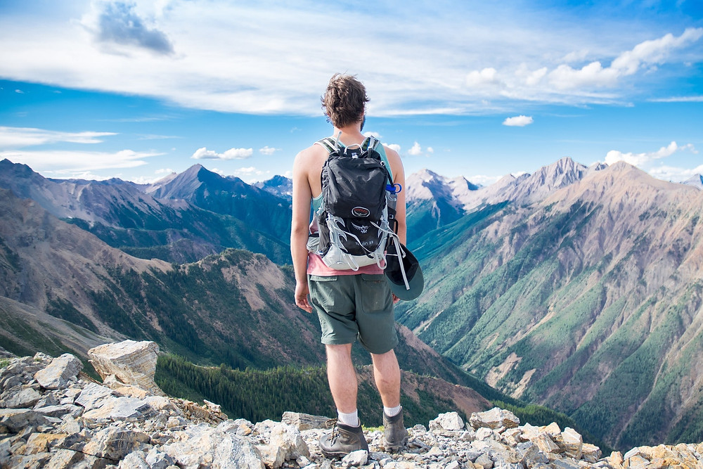 A man with an eco friendly backpack stands overlooking some mountains