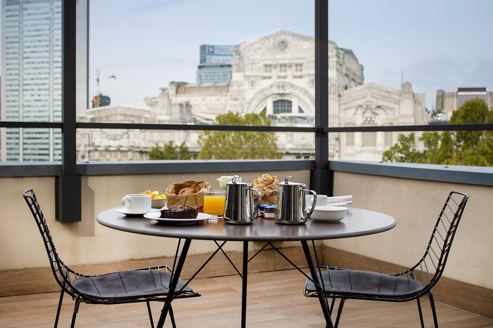 A breakfast set upon the table on the rooftop terrace of the eco-friendly Starhotels E.C.H.O in Milan