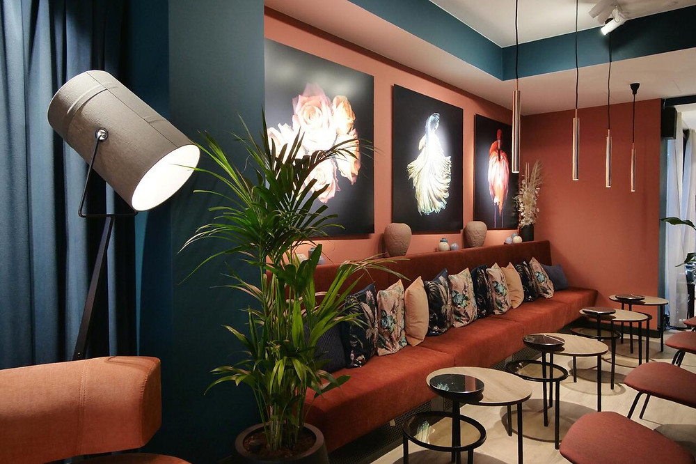 A stylish lounge area with red sofas inside the H27 green hotel in Copenhagen.
