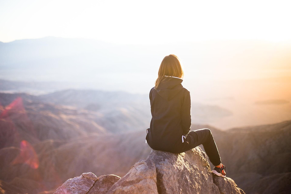 A woman in an eco friendly jacket sits on a mountain and watches the sun rise