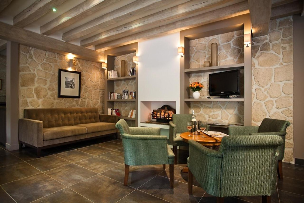 A sofa and two armchairs in front of a handsome stone wall at the eco-friendly hotel in Paris, Hotel du Printemps