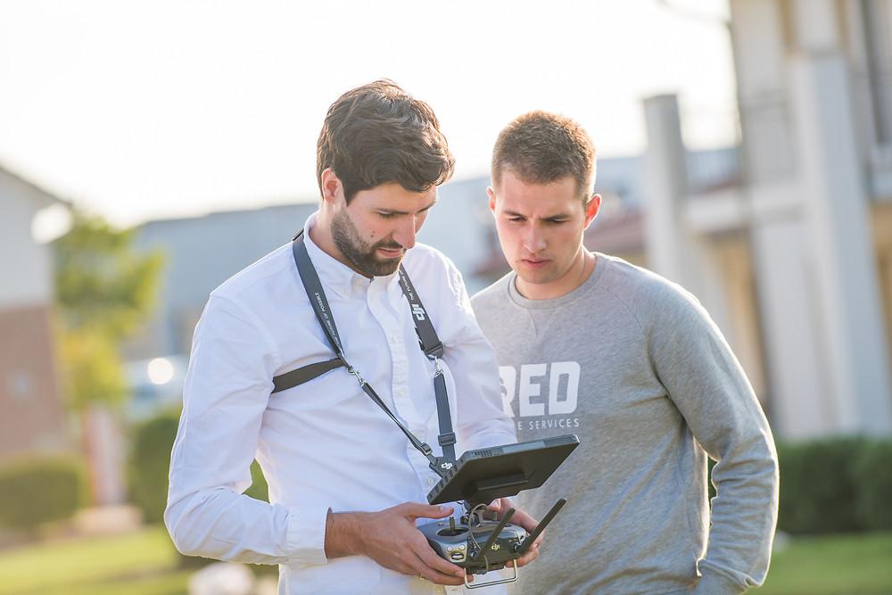 zwei Piloten steuern eine Drohne des Typs DJI Inspire 2 über die Fernbedienung.