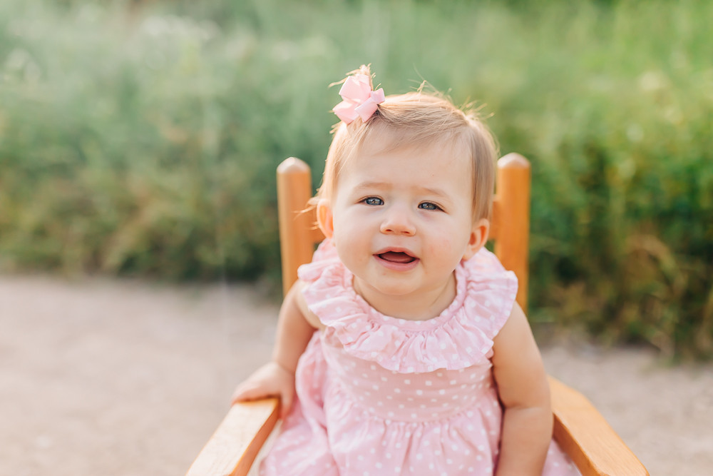 Nine month old little girl sitting in a wooden rocking chair for her milestone photography session with knoxville family photographer sweetest moments photography