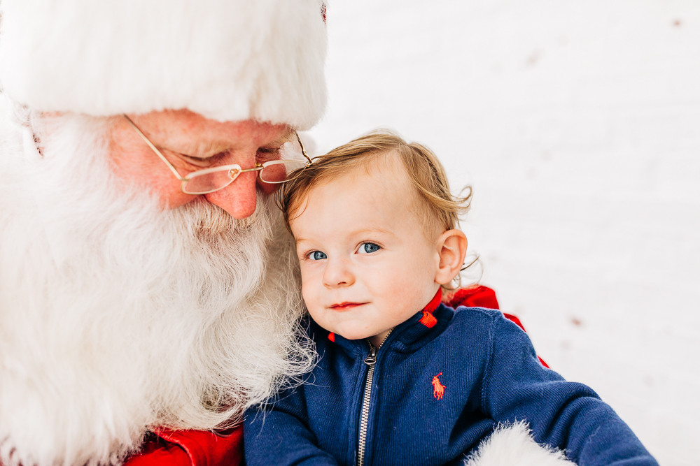One year old boy snuggled with Santa at the bleak house in knoxville tennessee for his santa mini session photography session with sweetest moments photography