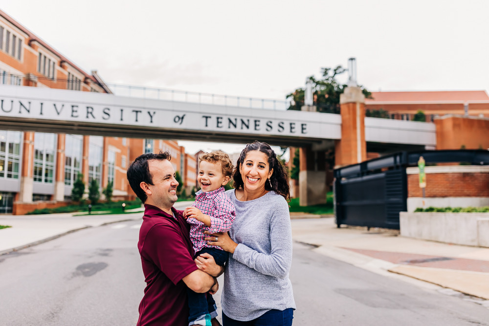 Family of three snuggling up at the university of tennessee campus with the pedestrian bridge behind the family captured by sweetest moments photography in knoxville tn