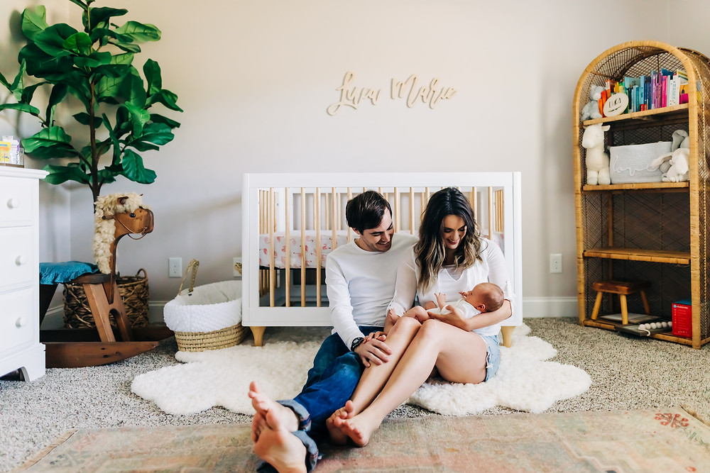 Parents in baby nursery sitting on floor in front of crib holding and smiling at newborn baby captured by Sweetest Moments Photography in Knoxville, TN