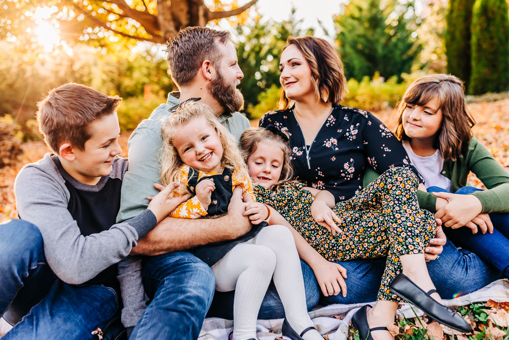 Family of seven under a maple tree snuggling on a blanket for their fall family photo session with knoxville family photographer sweetest moments photography located in knoxville tn