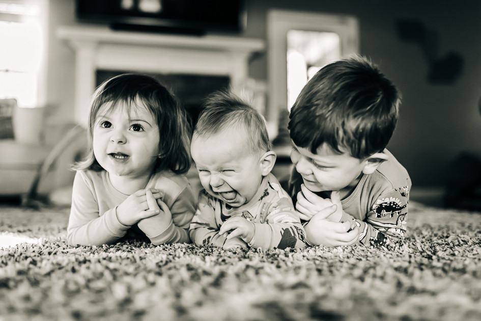 A black and white image captured by Sweetest Moments Photography in Knoxville, Tennessee of three young children laying on a rug in a living room laughing.