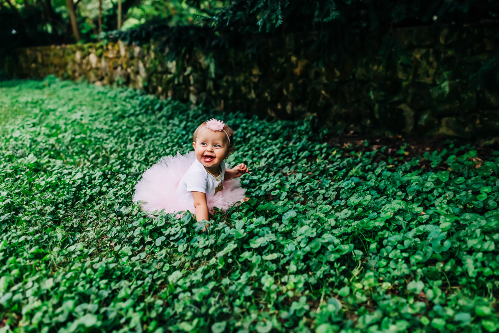 little one year old girl in a bed of clover in a white onesite and pink tutu for her one year old birthday milestone session at the knoxville botanical gardens with sweetest moments photography