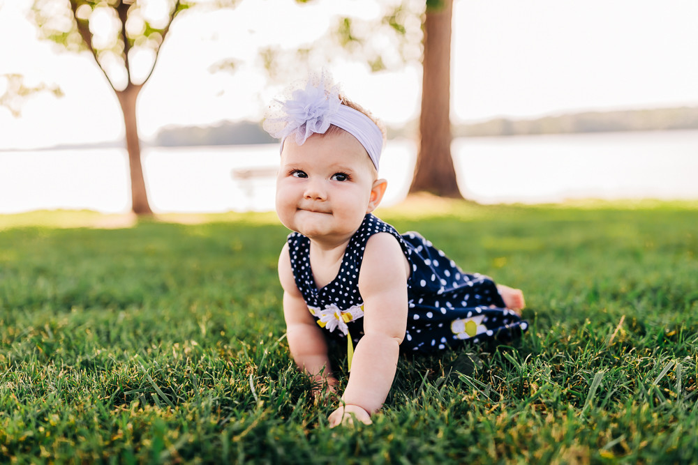 7 month old little girl doing tummy time in grass for her milestone photography session with sweetest moments photography at the cove at concord park in knoxville tn