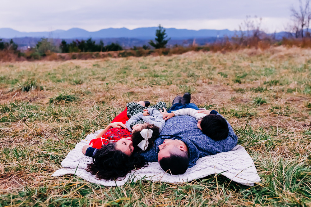 family of four snuggled up on a blanket for their fall family photography session with a mountain view by knoxville family photographer sweetest moments photography by hannah bucklin