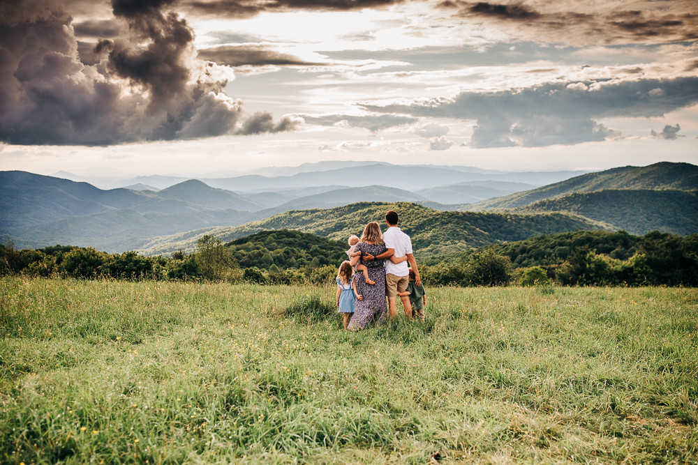 Photograph of a family of five staring into the mountains on the appalachian trail at max patch north carolina captured by sweetest moments photography located in knoxville tn