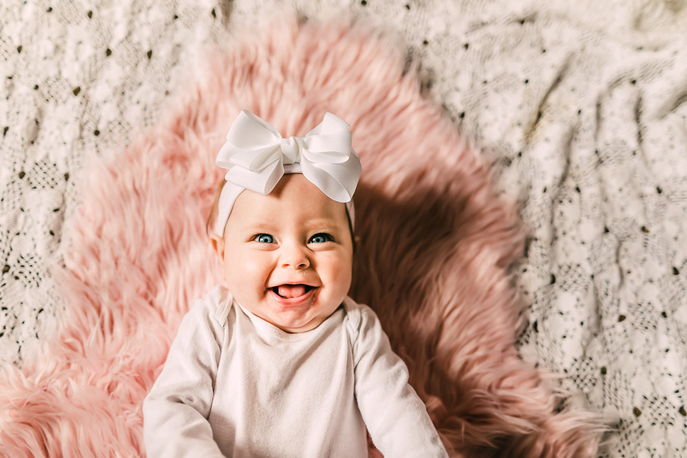 Baby girl laying on a faux pink rug with white lace behind it smiling at the camera with a white long sleeve onesie and a big white bow smiling at Knoxville family photographer Sweetest Moments Photography for her six month old milestone photography session in Greeneville, Tennessee.