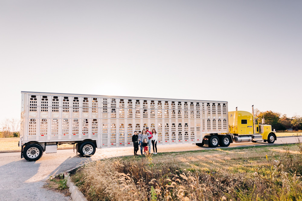 Family of seven standing in front of a cattle hauler semi for their annual fall family photography session with sweetest moments photography in knoxville tn