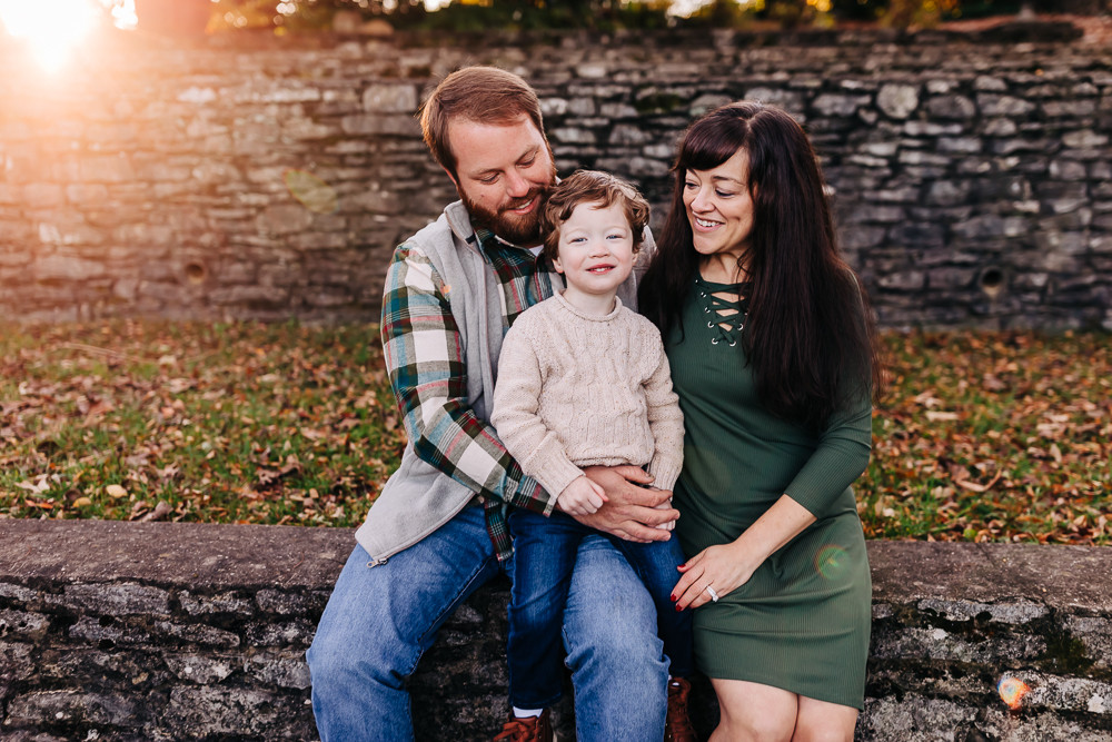 Family of three sitting down on a stone wall snuggled together for their fall family photography session with sweetest moments photography at knoxville botanical gardens in knoxville tn