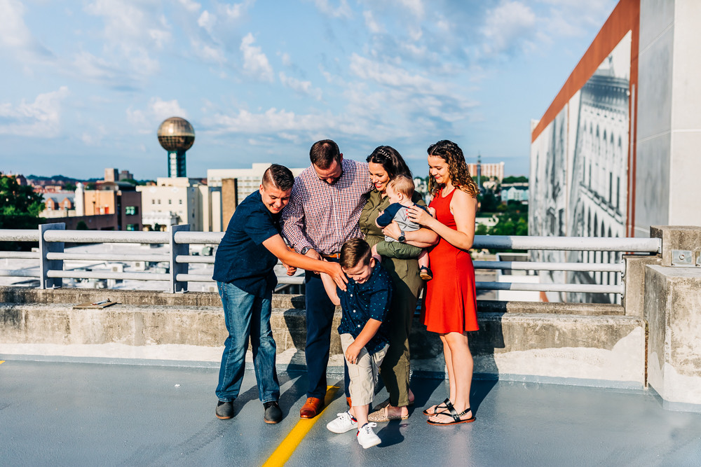 Family of six standing and snuggling on top of market square parking garage in knoxville tn for their family photography session with sweetest moments photography by hannah bucklin