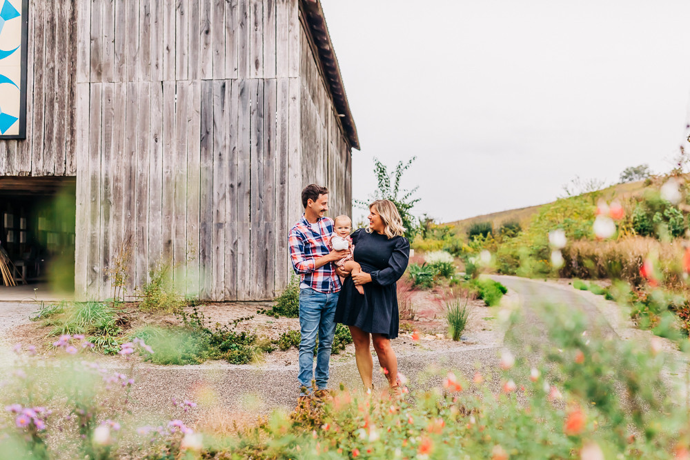 family of three by a rustic barn at seven islands state birding park in kodak tennessee taking their fall family photographs with family photographer sweetest moments photography in knoxville tn