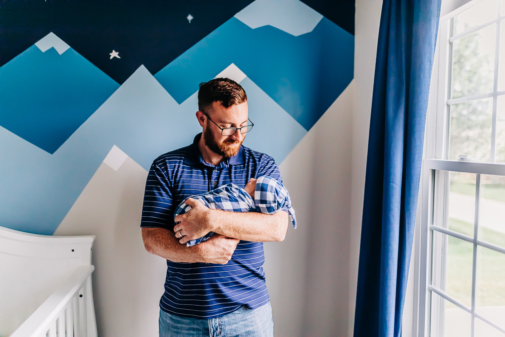 dad in the nursery of his newborn baby boy holding him as he is swaddled in a blanket during his lifestyle newborn photography session with knoxville newborn photographer sweetest moments photography
