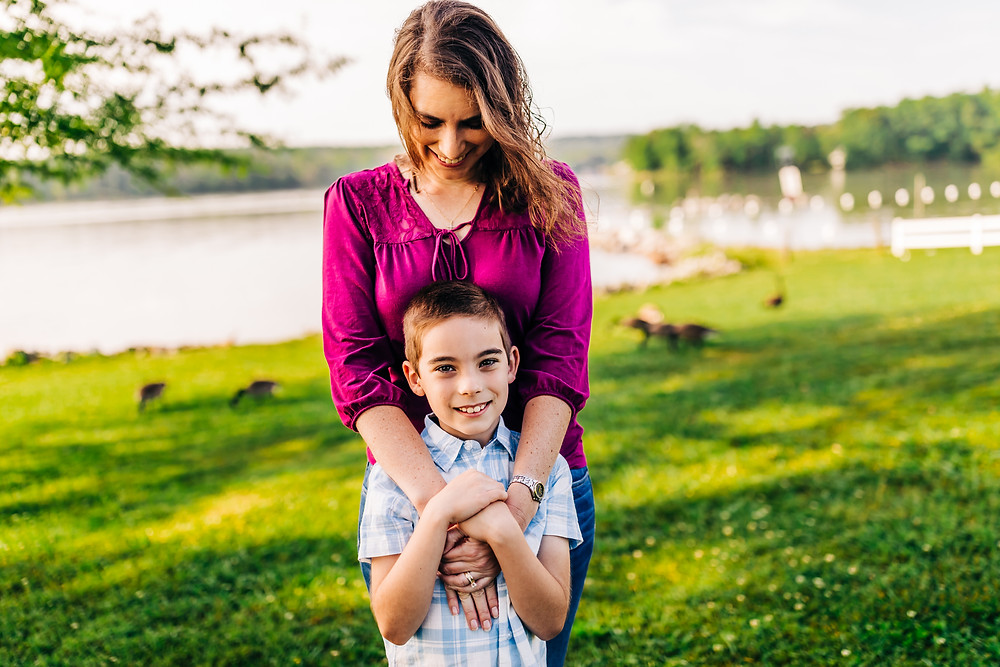 Mother wrapping her arms around her son on an early morning at the lake with geese in the background and wind blowing through her hair during golden hour captured by sweetest moments photography by hannah bucklin a knoxville family photographer