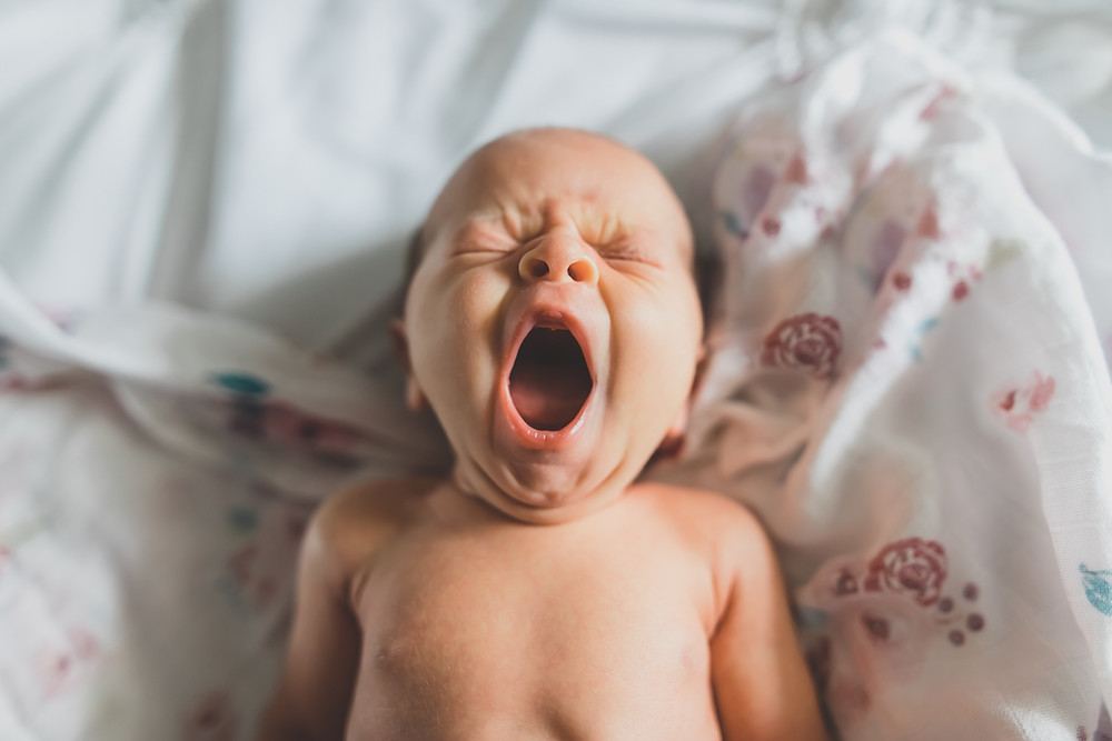 Newborn baby laying on the bed yawning after being unswaddled taken by knoxville family photographer Sweetest Moments Photography