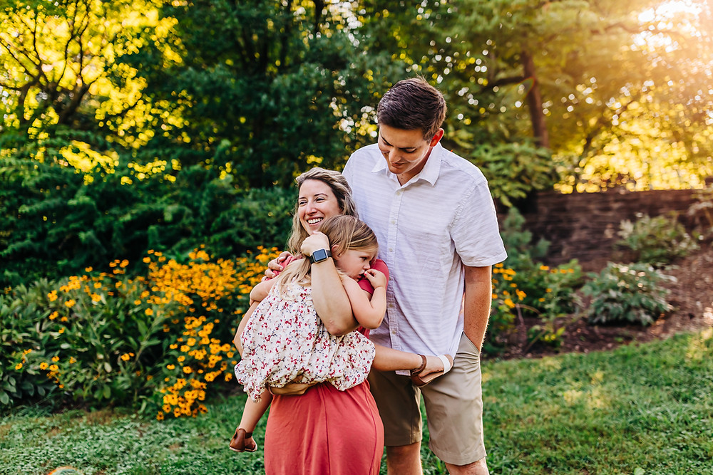 Family of three standing and snuggling each other in the early morning with golden glow through the trees at knoxville botanical gardens in knoxville tn captured by sweetest moments photography