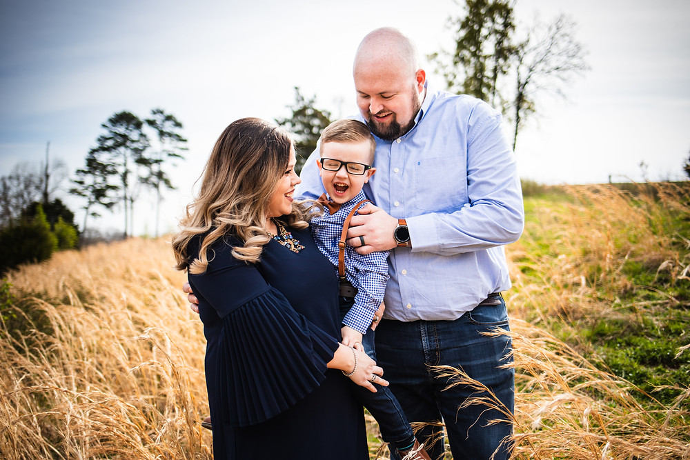 Family of three in a field with tall golden grass interacting with three year old son during their Easter mini session with family photographer Sweetest Moments Photography.