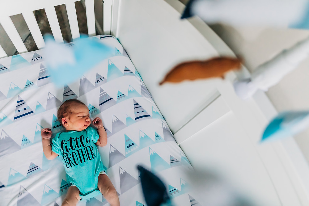newborn baby boy laying in crib while newborn photographer sweetest moments photography captures this picture looking through handmade mobile