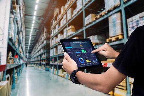 Smart warehouse management system.Worker hands holding tablet on blurred warehouse as back