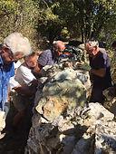 Un groupe de 4 bâtisseurs construit un mur en pierre sèche
